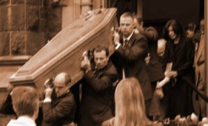 Alice Keilar follows pallbearers carrying her husband Brendan's casket from the church.